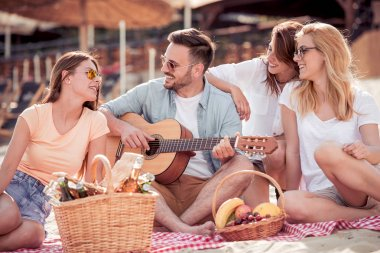 Four friends enjoying having picnic on beach with music and drinks