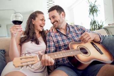 Handsome man playing some music on the guitar to his girlfriend.