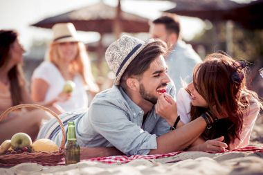 Happy young couple enjoying picnic on beach and have good time on summer vacation
