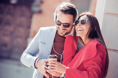 Happy couple with headphones sharing music from smartphone on street