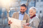 Happy mature couple of travellers holding map in hands.