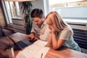 Mladý pár, Správa financí, pomocí přenosného počítače a Kalkulačka. Žena a muž dělá papíry pohromadě, platící daně online.
