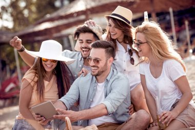 Group of friends taking selfie together on smartphone on beach