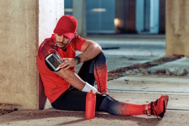 Handsome male jogger listening to music while taking break after morning training.
