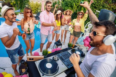Dj playing music at  pool party.People,music,happiness and fun concept.