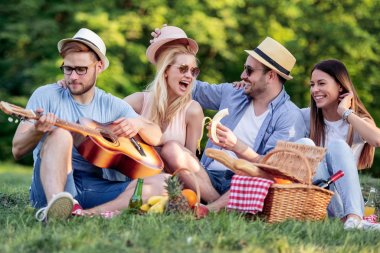 Happy young friends having picnic in the park.They are happy,having fun,smiling and playing guitar