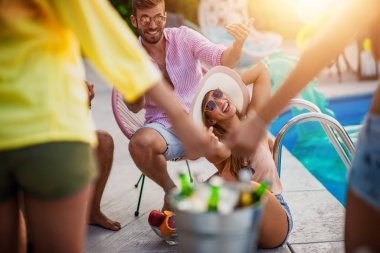 Group of friends having party in pool, drinking beers and enjoying together.