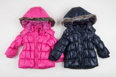 Two, cute blue and pink children's winter jackets stock vector