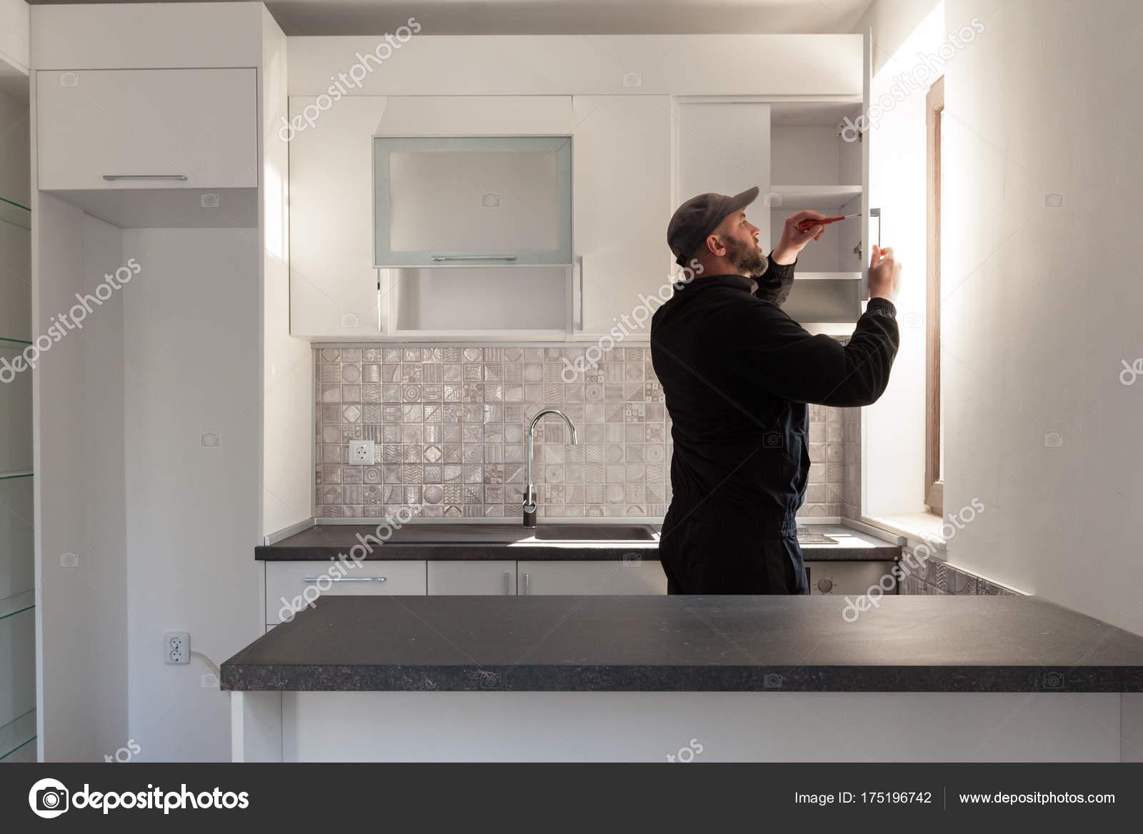 Tischler arbeiten an neuen Küche. Handwerker, die Befestigung einer ...