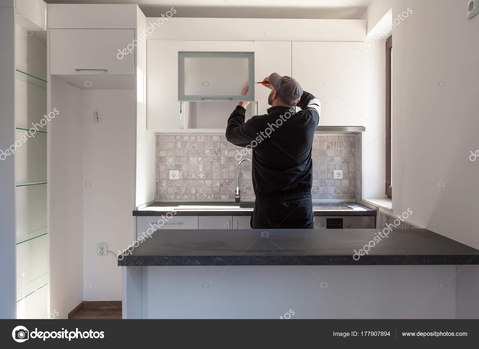 Carpintero trabajando en la nueva cocina. Fijación de una puerta en ...