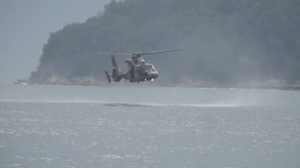 Vojáku, záchranná helikoptéra se vznáší nízko nad vodou, během záchranné mise. Záchranná helikoptéra při nízkém vznášedle. Zpomalený pohyb