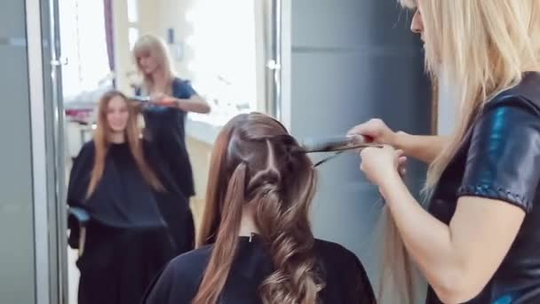 Hair stylist makes professional hairstyle of young woman in beauty studio using curling irons