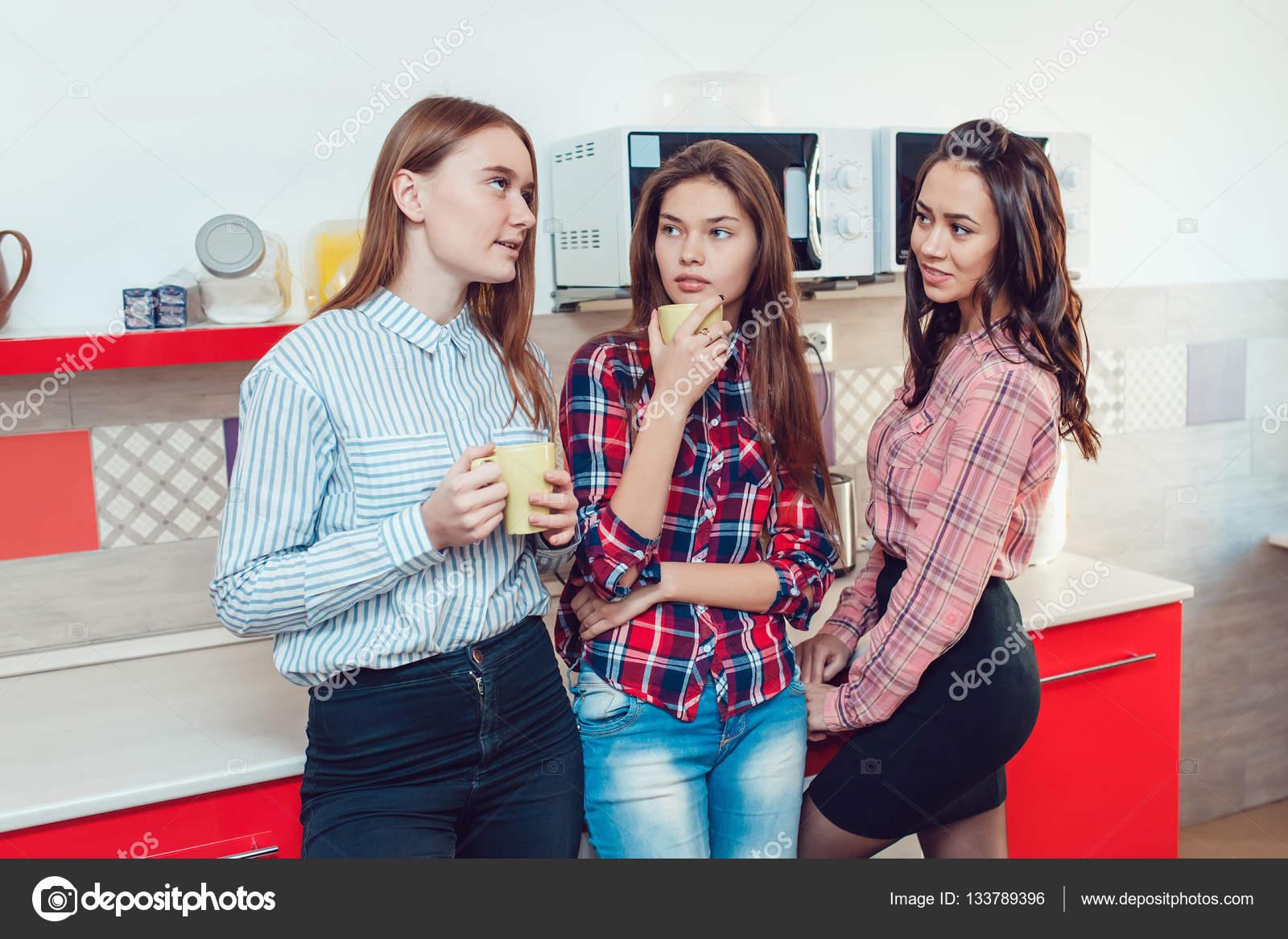 Schöne Mädchen stehen in der Küche der Herberge sprechen und trinken ...