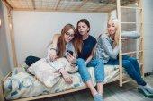 Gyönyörű lány ült egy ágyon a beszéd hostel, és használ smartphone.