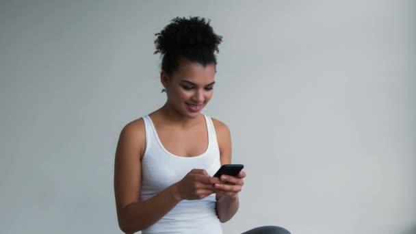 attraktive lächelnde afrikanisch-amerikanische Frau mit Make-up per Smartphone.