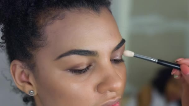 Professional make-up artist makes makeup of afro-american model. Beauty and fashion concept.
