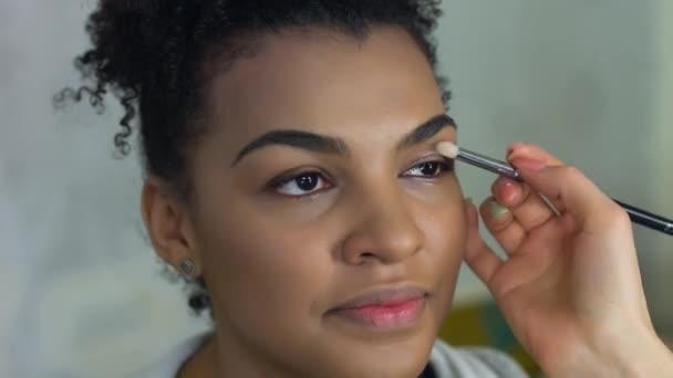 Profesionální vizážistka dělá make-up afro-american modelu. Krása a móda