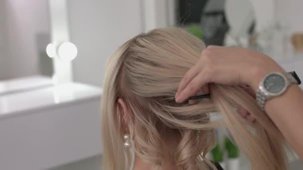 Kadeřnice dělá kadeře na dívku, pomocí vlasový styling. Kadeřník v práci.