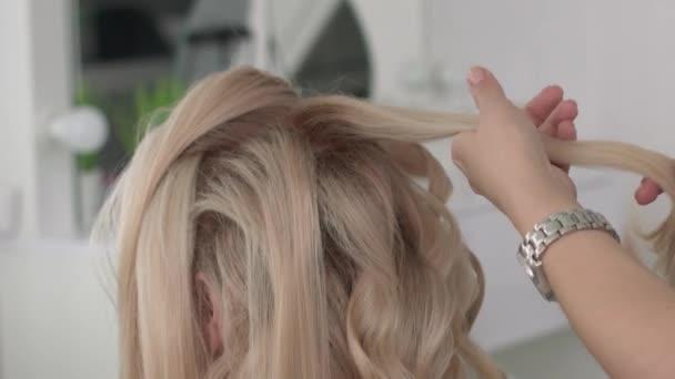Fodrász teszi a fürtök egy lány, haj stílus használata. Fodrászat, munkahelyi.