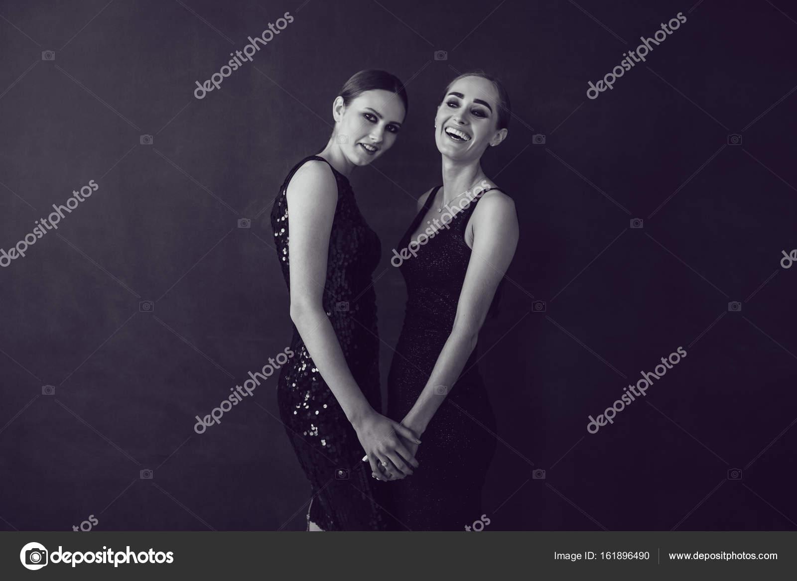 e67b45aa6a Due belle donne in moda nera notte vestono in posa su uno sfondo ...