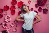 Fotografie Sexy Frau in einem weißen T-shirt auf einem rosa Hintergrund mit Blumen