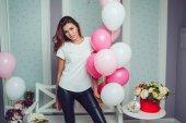 Fotografie Attraktives Mädchen in einem weißen T-shirt hält Luftballons. Mock-up