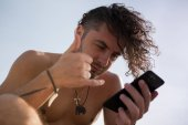 A man with curly hair uses a smartphone.