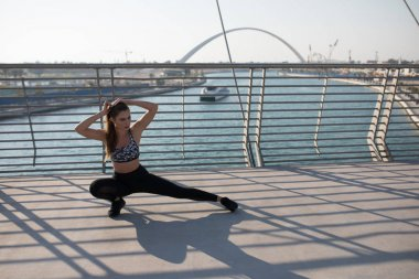 Sports woman doing stretching exercises on a bridge.