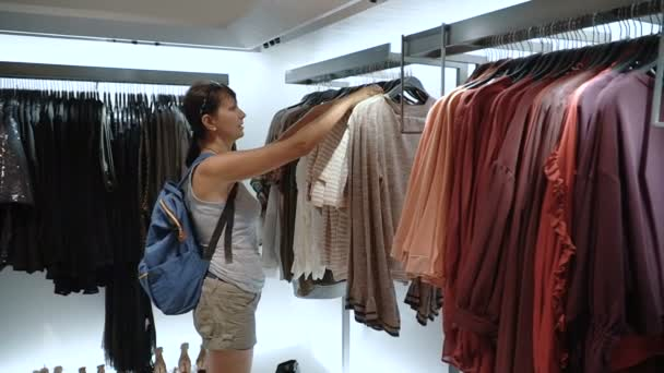 Mulher olhando roupas na loja de roupas — Vídeo de Stock ... 9d1daebb48dd9