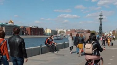 People stroll along the embankment of the Moscow River
