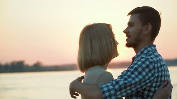 Milující pár se drží při západu slunce