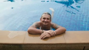 Man relaxing in hotel pool