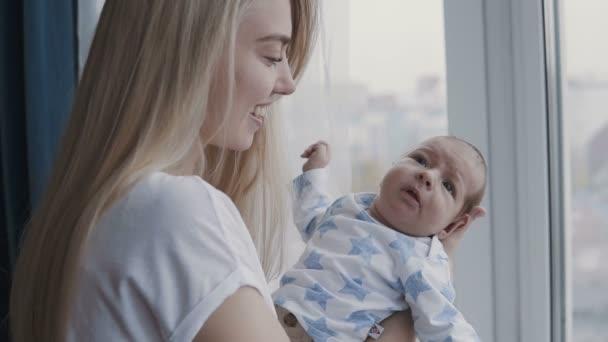 Šťastná mladá rodina - mladá matka drží svého novorozeného syna, líbá a objímá. Šťastný rodinný koncept. Zpomalení videa.