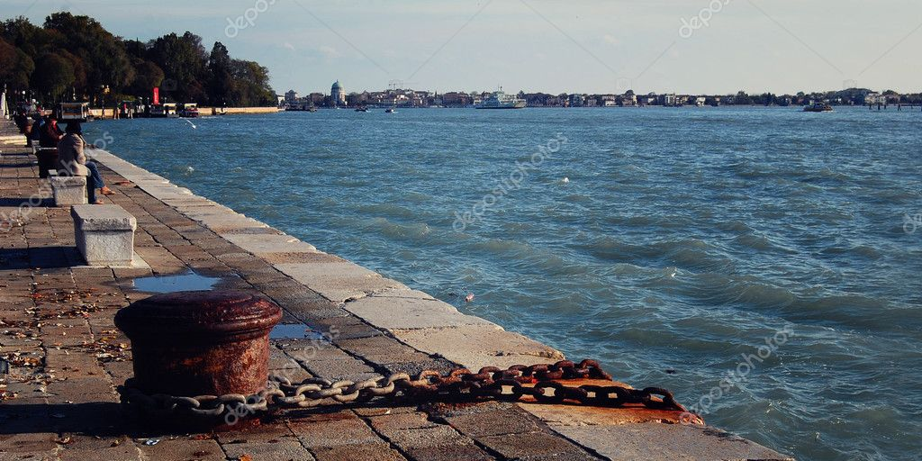 Old mooring bollard and rusty chain. Venice.