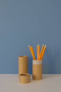 Paper tubes with yellow pencils on blue background. Recycle concept showing how to reuse paper tubes at home. Copy space. Vertical photo