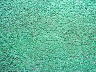 Decorative cracked plastered wall as creative background with copy space for your text. Real green stucco texture