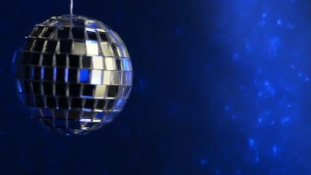 Zrcadlová diskotéka se otáčí. Osvětleno neonem na modrém pozadí.