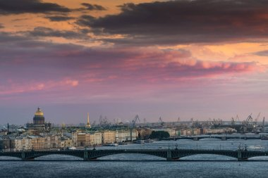 Beautiful summer aerial sunset view over Neva river and Saint Petersburg cityscape: Troitsky bridge, Winter Palace, Saint Isaac's Cathedral, and port cranes in the distance