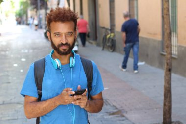close-up portrait of handsome young man listening music with headphones on street