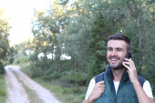 close-up portrait of handsome young man talking by phone on nature