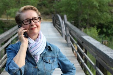 Mature woman in glasses using a smart phone outdoors
