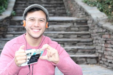close-up portrait of handsome young man in casual clothes listening music with vintage headphones and player on city street