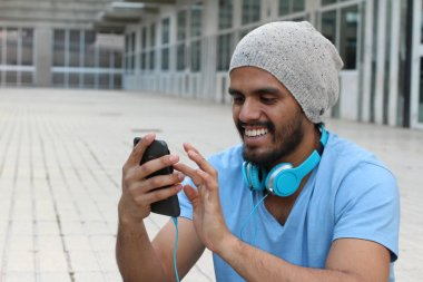 close-up portrait of handsome young man using smartphone on street