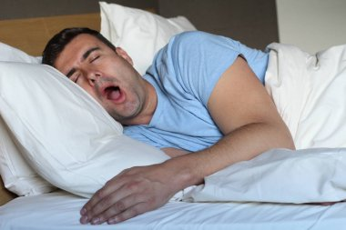 Ethnic man deeply slept in comfy bed