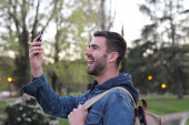 close-up portrait of handsome young man with backpack using smartphone in park in evening