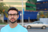 Portré jóképű férfi szemüvegben áll a szabadban, homályos háttér