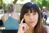 Portré szépség barna nő ül kávézóban a nyári parkban, homályos háttér