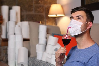 Man stocking up toilet paper and drinking wine at home