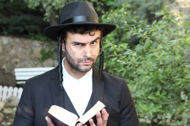 close-up portrait of handsome young rabbi in traditional hat with Tanakh on natural background