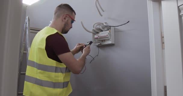 samec elektroinženýr kontroluje připojení a napětí v místnosti domu nebo stavby.